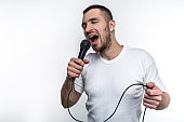 Emotional man is singing song in microphone and rocking out. He is enjoying doing that. Isolated on white background.