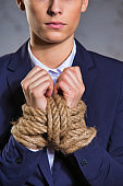 Portrait of young businesswoman standing with tied hands at office