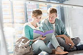 Young man and woman reading book while sitting on corridor at university