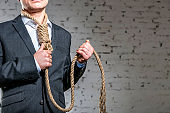 Midsection of businessman with rope noose standing against brick wall at office