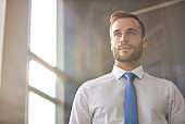 Handsome young businessman looking away while standing in new office