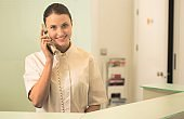 Smiling young receptionist talking on phone at checkout counter