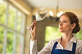 Confident young waitress looking at empty wineglass in restaurant
