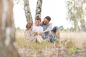 Happy family sitting against tree on field at farmland