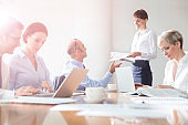 Modern officeSmiling businesswoman giving documents to businessman by colleagues during meeting in boardroom at modern office