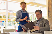 Young waiter taking orders from customer at restaurant