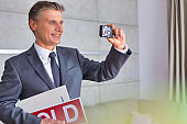 Mature man taking photo of home interiors while holding red placard