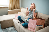 Online shopping at home. Young happy woman with is waiting for beggining of black Friday while sitting on a sofa with shopping bags