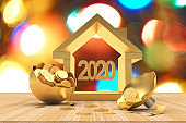2020 house icon with coins and blurry bokeh lights.