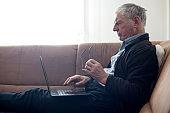 Senior Man Using Laptop on Sofa in Living Room
