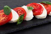 Caprese salad. Mozzarella cheese, tomatoes and basil herb leaves over stone table