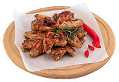 Grilled chicken wings on wooden cutting board isolated on white background