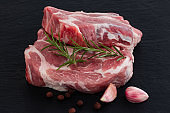 Raw meat,  steak with spices on black background