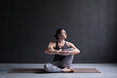 Woman working out, doing yoga exercise on floor, Needle hip stretch pose