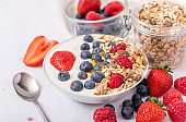 White yogurt in bowl with oatmeal and strawberries, blueberries and raspberries on the top on white background