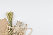 eco natural paper cups, string bag, wheat. flat lay on white background