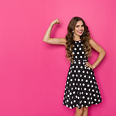 Elegant Strong Woman In Cocktail Dress Is Flexing Muscles And Smiling
