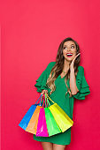 Young Fashion Woman Is Holding Colorful Shopping Bags, Looking Up And Laughing