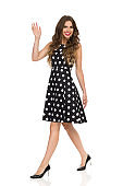 Beautiful Young Woman In Black Dotted Cocktail Dress And High Heels Is Walking And Waving Hand