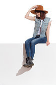 Young Woman In Jeans Vest, Boots And Suede Hat Is Sitting On A Top And Looking Down