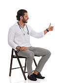 Male Doctor Sitting On A Chair And Showing Thumb Up. Side View.