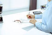 Unknown female bookkeeper or financial inspector calculating or checking balance, making report, close-up. Internal Revenue Service at work with financial document. Tax and audit concept.