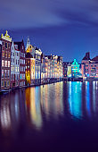 Cityscape with famous buildings in Amsterdam at night.