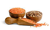 Lentils in a wooden bowls and scoop isolated on white background.