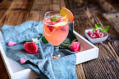 Delicious raspberry peach mimosa drink on a wooden background