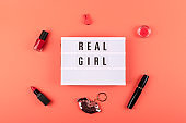 Real girl text on lightbox and decorative cosmetics on coral background. Beauty, makeup flat lay