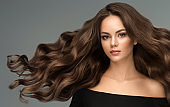 Young, brown haired beautiful model with long,  curly, well groomed hair. Excellent hair waves. Hairdressing art and hair care.