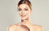 Gorgeous, young woman dressed in a soft, elegant makeup is touching the face by graceful fingers. Beauty and cosmetology.