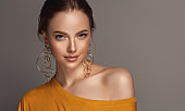 Misty look and tender smile on the perfect face of model dressed in a mustard color t-shirt.