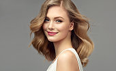 Portrait of young woman with dark blonde hair. Cosmetology, hairdressing and makeup.