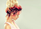 Attractive woman is demonstrating multi colored hair gathered in elegant evening hairstyle.