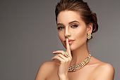 Alluring woman dressed in a posh jewelry set of necklace, ring and earrings. Elegant evening style.