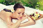 Relaxing, full of pleasure smile on the face of young, appealing woman. Lady is laying on massage table and getting stone therapy.