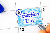 Woman fingers with blue pen writing reminder Election Day in calendar. November 5.