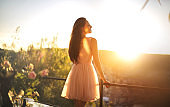 Beautiful girl enjoying the sunset from a terrace