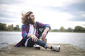 Handsome alternative guy sitting on a pier, relaxing