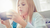 Close-Up Portrait of a Smart Cute Girl Sitting on a Carpet at Home Playing in Video Game on His Smartphone, Holds and Uses Mobile Phone in Horizontal Landscape Mode. Child Has Fun Playing Videogame in Sunny Living Room.