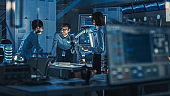 Diverse Team of Engineers with Laptop and a Tablet Analyse and Discuss How a Futuristic Robotic Arm Works and Moves a Metal Object. They are in a High Tech Research Laboratory with Modern Equipment.