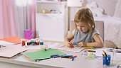 Cute Little Girl Sits at Her Table and Draws with Crayons. Her Room Is Pink, Pretty Drawings Hanging on the Walls, Many Toys Lying Around.
