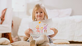 Cute Young Smiling Girl Sitting on Pillows and Shows Drawing of Her Family. Sunny Living Room.