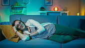 Beautiful Excited Young Girl in Glasses Lying Down on a Couch and Watching TV at Home. She is Smiling. Screen Adds Reflections to Her Face. Cozy Room is Lit with Warm Light.