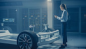 Automobile Engineer Working on Electric Car Chassis Platform, Using Tablet Computer Augmented Reality with 3D CAD Software Modelling. Innovative Facility: Vehicle Frame with Wheels, Engine, Battery