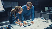 In the Dark Industrial Design Engineering Facility Male and Female Engineers Talk and Work on a Blueprints Using Digital Tablet and Conference Table. On the Desktop Drawings and Engine Components