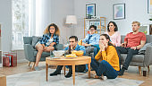 At Home Diverse Group Friends Watching TV Together, Getting Emotionally Terrified and Horrified by the Content of the TV. Young People Are Scared After Watching News or Horror Movies.
