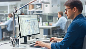 Over the Shoulder Shot of Engineer Working with CAD Software on Desktop Computer, Screen Shows Technical Drafts and Drawings. In the Background Engineering Facility Specialising on Industrial Design