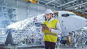 Aircraft Maintenance Mechanics Moving through Hangar. Holding Tablet Computer
